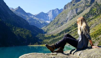 Tourist sitting on rock at Gaube lake. Hautes Pyrenees, France.