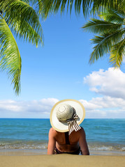 Caucasian girl with hat lying on the tropical sand beach. Summer vacation by the sea.