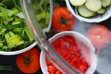 A glass cover from a saucepan is hold in front of washed carved vegetables, leek, couchette, tomatoes and paprika.