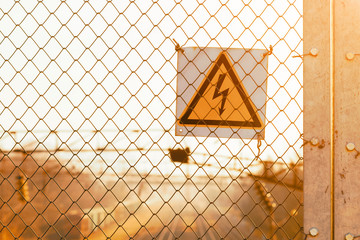 Yellow high voltage warning sign on an iron mesh fence over railroad tracks at sunset with copy space.