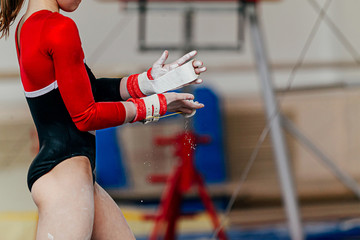 girl gymnast in gymnastics hand grips and gym chalk