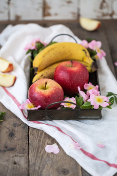 Apples and banannas on a metal tray with flowers