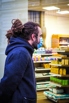 Handsome young European man in winter clothes on the street with a medical face mask on looking inside the pharmacy through the shop window