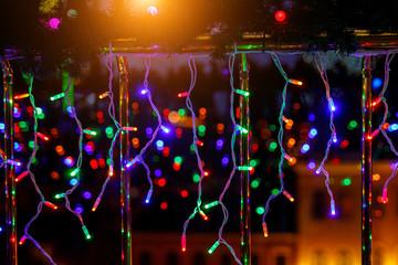 Multicolor garlands on dark background, christmas lights.