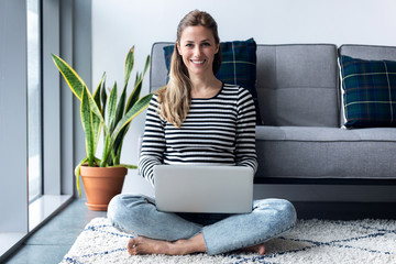 Obraz Pretty young woman looking at camera while using her laptop at home. - fototapety do salonu