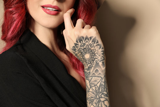 Beautiful woman with tattoos on arm against beige background, closeup