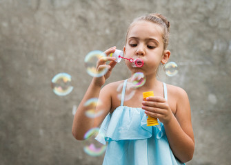 Cute little girl in blue dress blowing bubbles