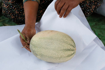 A worker packs a melon to send to Yangon for sale in Madauk, Bago