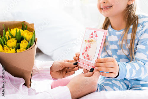 cropped view of smiling daughter giving card to mother in international womens day