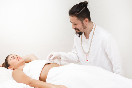 Oriental medicine doctor doing acupuncture stomachs to relieve a woman's stomach pain. Alternative medicine