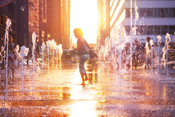 Child run and play on street fountain on Philadelphia square over sunset near city hall in downtown