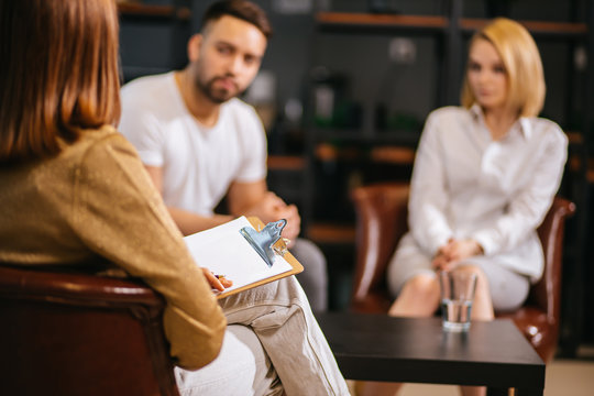 unhappy married couple talking to family psychologist before breaking up, consulting family relationships expert, trying to save married couple. relationships, people, family, psychology concept