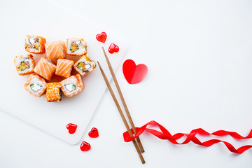Valentine's Day. Sushi and sticks on a white background. The concept of a romantic dinner at a sushi bar. The portfolio has more images by February 14th.