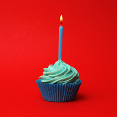 Delicious birthday cupcake with turquoise cream and burning candle on red background