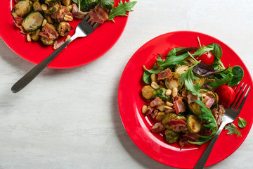 Salad with roasted brussels sprouts and bacon on white wooden table, flat lay