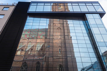 Wroclaw, Poland - December 2, 2019: St Mary Magdalene church reflected in modern building facade in historic part of Wroclaw city
