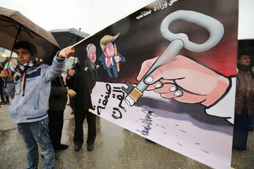 """Protesters hold caricature image reading in Arabic """"No right will be lost as demands continue"""" during a protest against U.S. President Donald Trump's proposed Middle East peace plan, near the U.S. Embassy in Amman"""