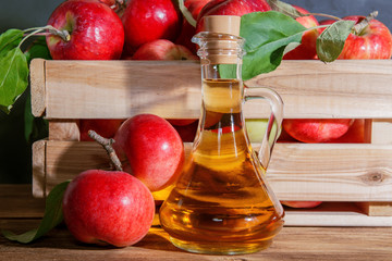 Homemade fruit canning, diet healthy food and drink. Apple cider vinegar, juice, salad dressing from a crop of ripe red garden fruits in a glass jug on a wooden rustic background