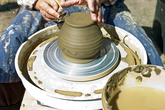 PETROZAVODSK,RUSSIA-JUNE 29TH,2019:The hands of a man who sits at the potter's wheel and works with a clay product