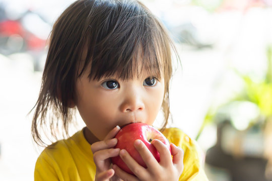 Portrait image of 1-2 yeas old of baby. Happy Asian child girl eating and biting an red apple. Enjoy eating moment. Healthy food and kid concept. Vintage style.