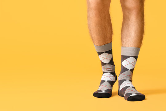 Male legs in socks on color background