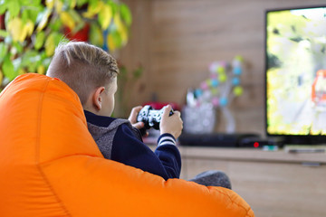 Young gamer boy playing online car racing game on new console at home tv