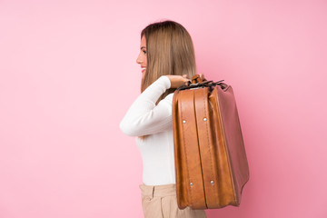 Young blonde woman over isolated pink background holding a vintage briefcase