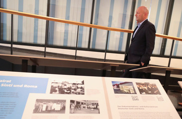 New Thuringia State Premier Minister Kemmerich of FDP walks past an exhibition showing the cruelty of the Nazi regime against the Sinti and Roma at the federal parliament in Erfurt