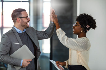 Businessman and businesswoman celebrating success by doing the high-five in office hall. Two business people high-five. Job well done. Two excited business colleagues team give high five