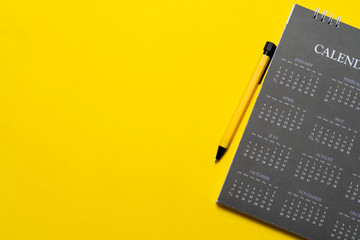 close up of calendar and pen on the yellow table background, planning for business meeting or travel planning concept