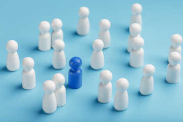 The leader of the blue color stands among the crowd, a group of white employees. The concept of leadership. Many employees are drawn to their boss. Personnel selection.