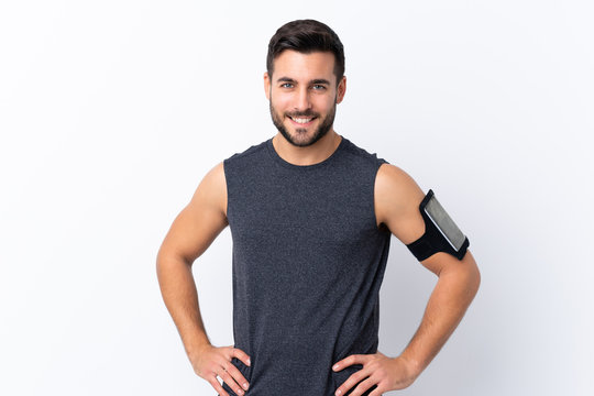 Young sport handsome man with beard over isolated white background posing with arms at hip and smiling
