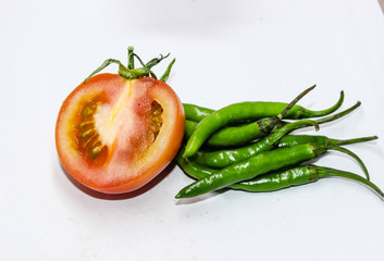 A picture of green chilies with fresh tomato