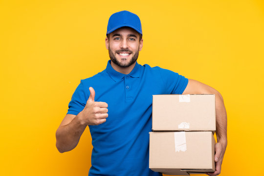 Delivery man over isolated yellow background with thumbs up because something good has happened