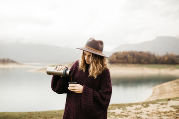 Tuinposter Art Studio Happy beautiful woman with hat drinking coffee in nature, on a foggy morning Lake and mountains are in the background. She is smiling and poring coffee.