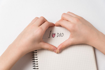 Child hands making heart shape with I love dad notice. Notebook with handwritten. Father's day