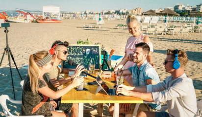 Happy friends having fun vlogging video live feed at beach party - Young influencer sharing content online with web cam on social media platforms - Modern technology concept on warm bright filter