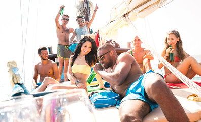Multiracial friends having fun at sailboat party with dj set - Wanderlust travel concept with young...