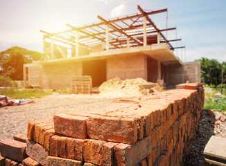 Pile of red bricks with blurred house under construction.