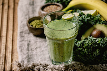 Glass of green healthy vegan smoothie, glass straw. Ingredients above. Kale, bananas, avocado, lime, non-diary milk, matcha powder and seeds over wooden plank cloth background. Close up
