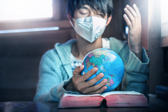 Close up hands of christian young man in mask, holding the globe and praying for peaple in the world, stop Disease Virus and War, christian concept.
