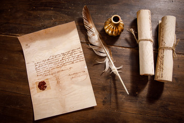 Quill pen, feather with a letter and a scroll on a wooden table.