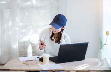 Young female wearing hat and glasses using mobile phone working with laptop in cafe