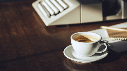 Close up coffee cup with sunlight on wooden desk and blurred old typewriter and notebook, Dark tone background