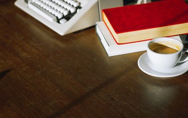 Place of work on wooden desk have old typewriter, note, book and coffee with sunlight in the morning. Retro style