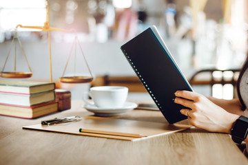 Female lawyer reading legal books while she working with on desk
