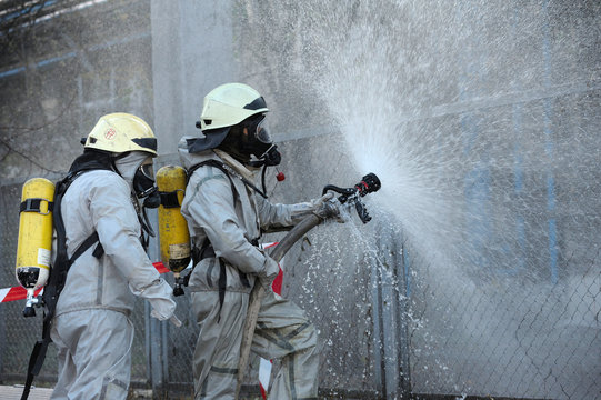 Rescuers in protective rubber suits watering plant territory with syringe. Rescue team training in decontamination