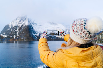 Tourist taking a smartphone picture at Hamnoy, Lofoten, Norway