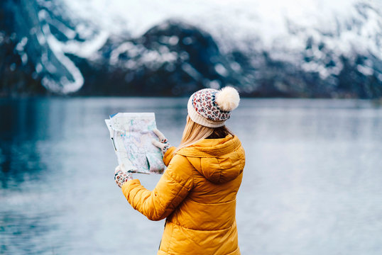Tourist reading a map at the coast in Hamnoy, Lofoten, Norway