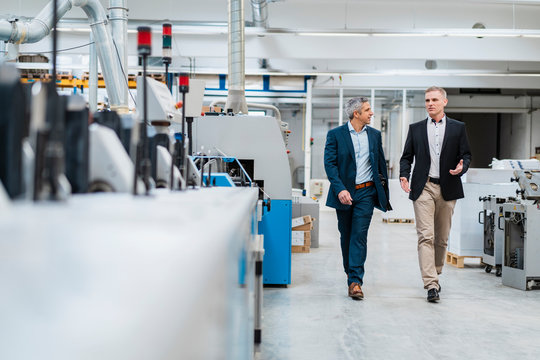 Two businessmen walking and talking in a factory
